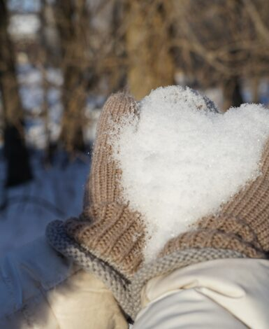 hands in brown mittens holding snow in a heart shape