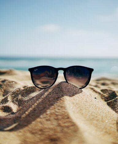 Sunglasses on a sand mound brings to mind summer break