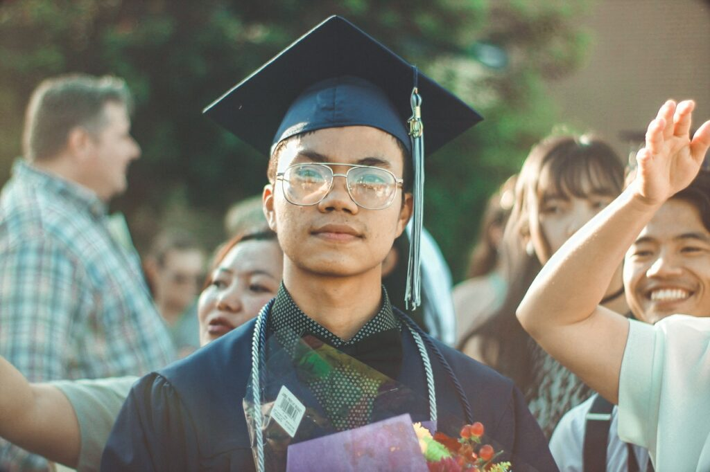 Graduate in cap and gown. Apply economics to your daily life by considering college an opportunity cost.