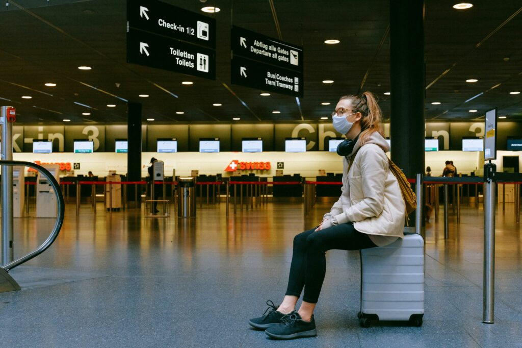 airline passenger sitting on suitcase in terminal - U.S. airline industry starting to recover