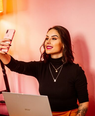 influencer marketing requires proper disclosure - woman takes a selfie against a pink wall