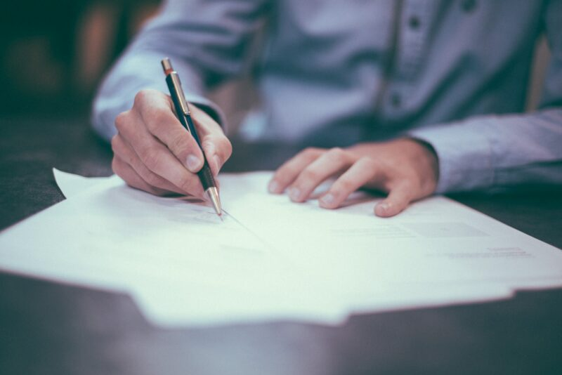 HR professionals and supervisors must be aware of multiple employment laws. Image of papers spread on a desk, focused on a hand holding a pen over the paper.