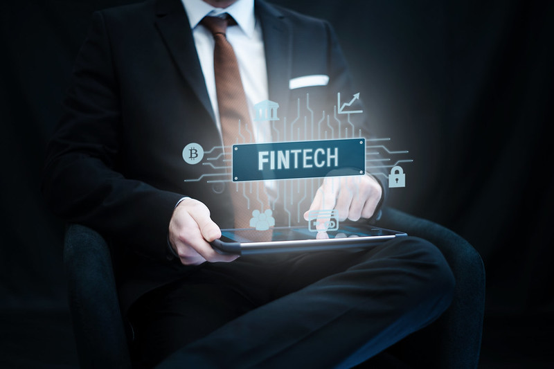 Man in suit uses tablet with word FinTech floating above it.